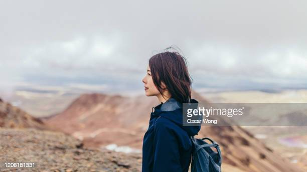 Young Woman Hiking On The Mountain Against Cloudy Sky