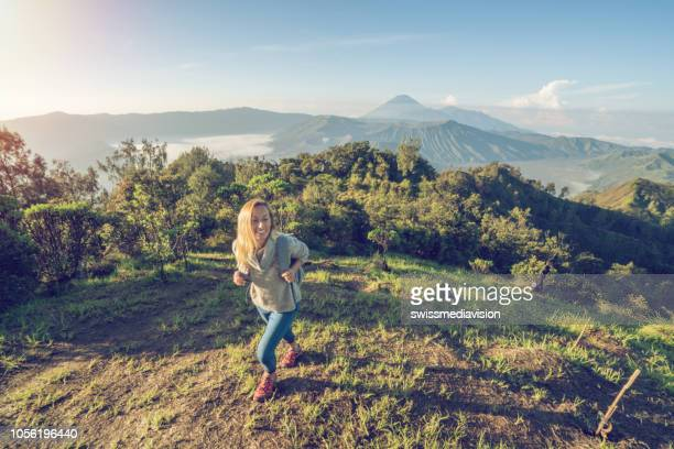 young woman hiking on volcanic landscape from top of hill looking at bromo volcanoes- people travel adventure concept - mt bromo stock pictures, royalty-free photos & images