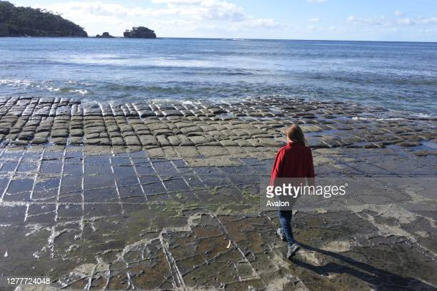 Young woman hiking over the Tessellated Pavement in Tasman Peninsula Tasmania Australia.