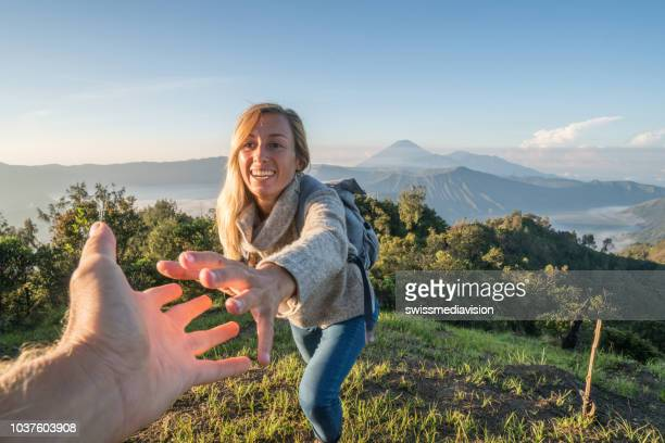 young woman hiking, pulls out hand to reach the one of teammate. a helping hand to reach the mountain top. bromo volcano region in indonesia, asia - active volcano stock pictures, royalty-free photos & images