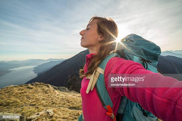 Junge Frau Wandern erreicht mountain top, outstretches Arme