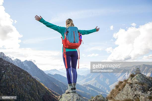 Junge Frau Wandern erreicht mountain top, outstretches Arme