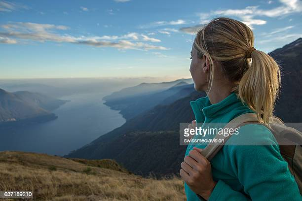 Young woman hiking reaches the mountain top, contemplates view