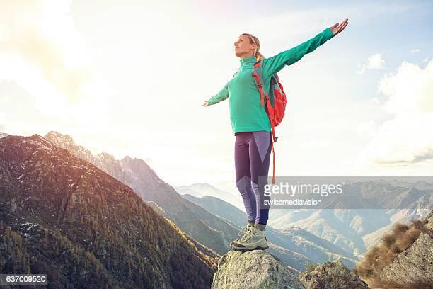 若い女性が山のハイキングのトップ、outstretches arms