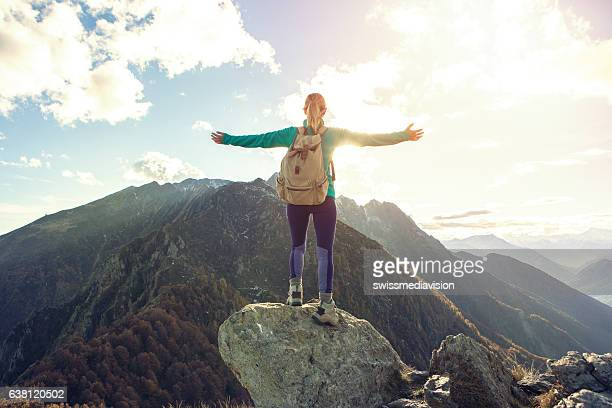 young woman hiking reaches the mountain top, outstretches arms - mountain peak stock pictures, royalty-free photos & images