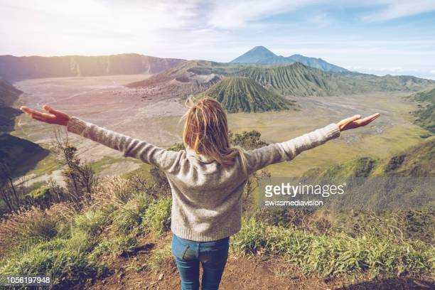 young woman hiking stands arms outstretched on top of mountain with bromo volcanoes view in indonesia- people travel fun adventure concept success and achievement - mt bromo stock photos and pictures