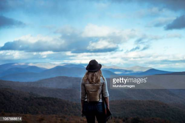 young woman hiking through beautiful mountains. - pilgrimage stock pictures, royalty-free photos & images