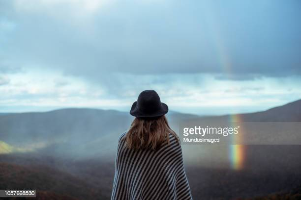 young woman hiking through beautiful mountains. - rainbow stock pictures, royalty-free photos & images