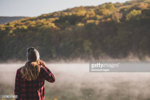 young woman hiking with coffee - november stock pictures, royalty-free photos & images