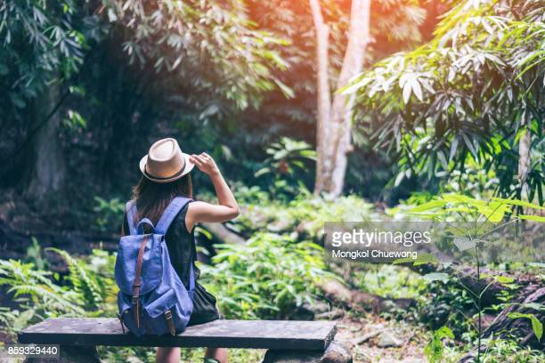 Young woman hipster travelver with backpack and hat sitting alone in tropical forest