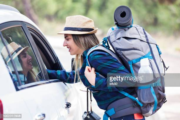 young woman hitchhiker asking a road to driver. - stranger stock pictures, royalty-free photos & images