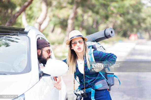 young woman hitchhiker asking a road to driver. - stranger stock photos and pictures