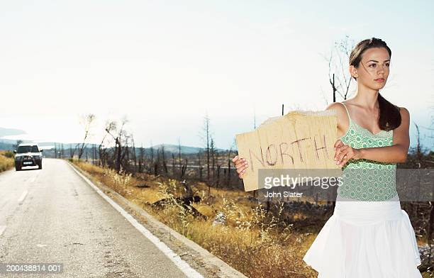 Young woman hitchhiking at side of road, holding up 'North' sign