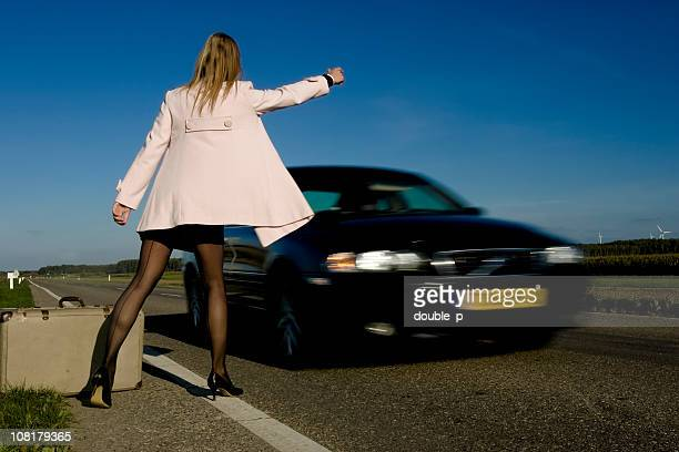 young woman hitchhiking on side of road with luggage - black women wearing pantyhose stock pictures, royalty-free photos & images