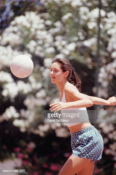 Young woman hitting volleyball outdoors