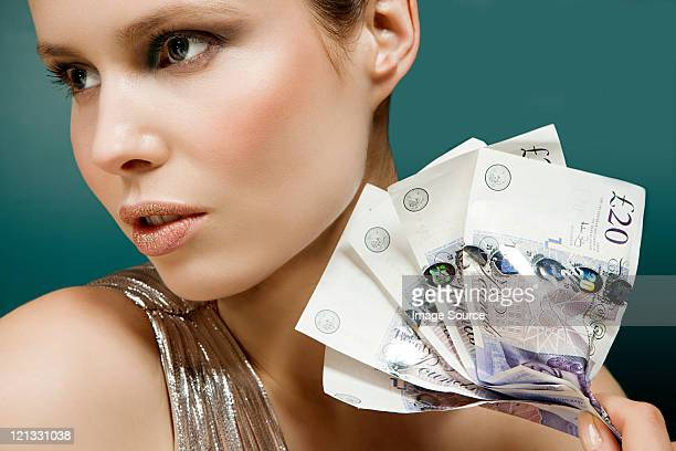 young woman holding 20 pound notes - british pound sterling note stock pictures, royalty-free photos & images