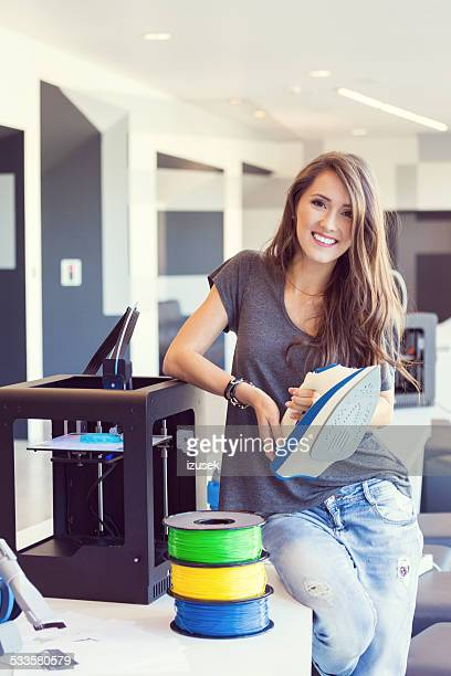 Young woman holding 3D printout - an iron