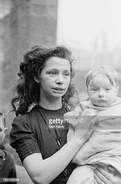 A young woman holding a baby wrapped in a blanket in the Gorbals a slum district of Glasgow 1948 Original publication Picture Post 4499 The Forgotten...