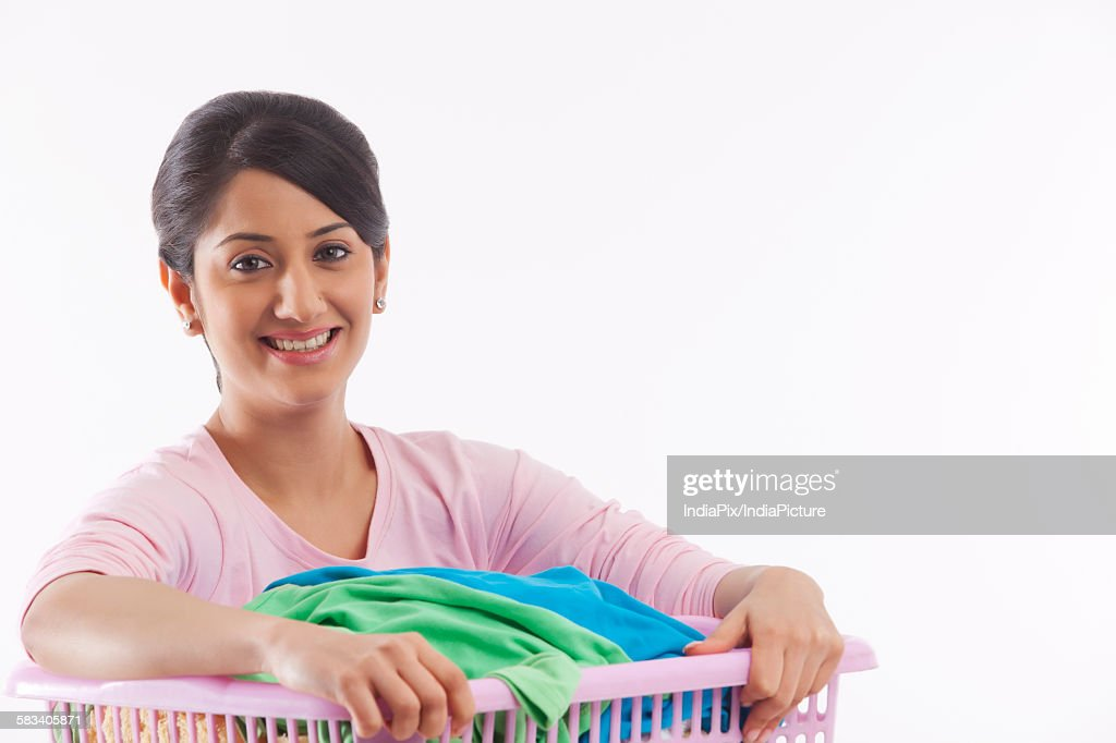 Young woman holding a basket of clothes : Stock Photo