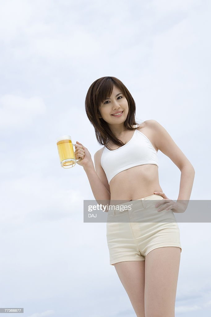Young woman holding a beer glass, low angle view : Stock Photo