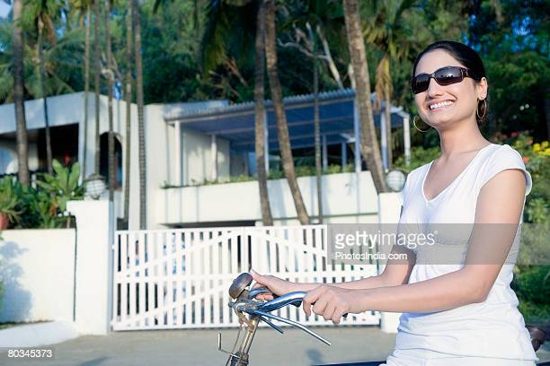 Young woman holding a bicycle and smiling