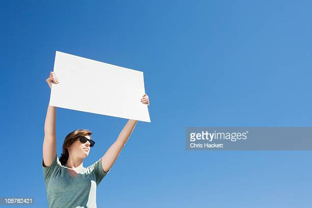 young woman holding a blank placard - blank sign stock photos and pictures