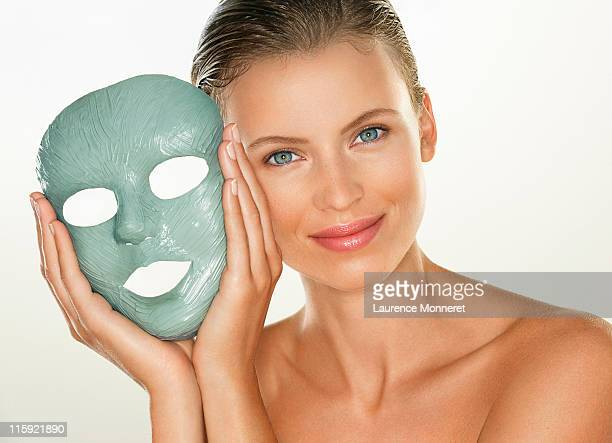 Young woman holding a blue clay care mask