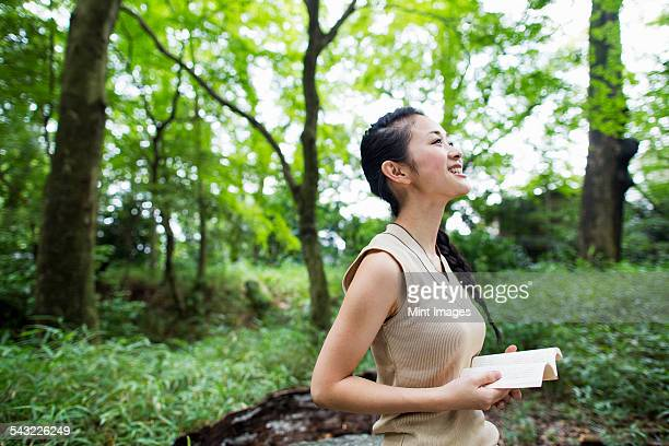 Young woman holding a book in a forest.
