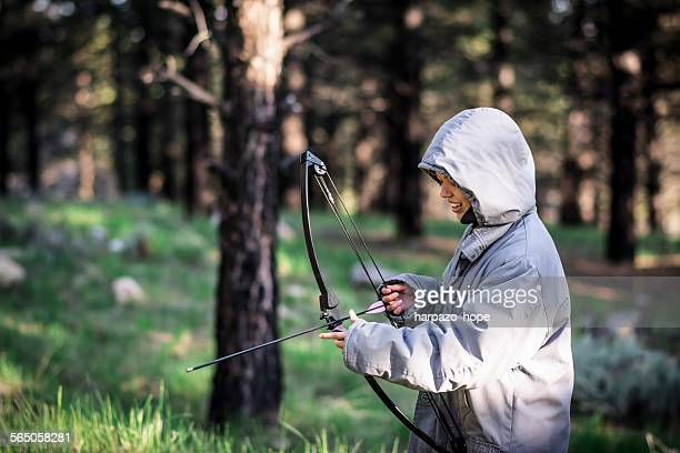 Young woman holding a bow and arrow