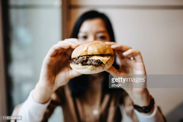 young woman holding a burger in front of her face and ready to bite into it - biting stock pictures, royalty-free photos & images