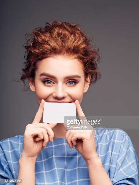 young woman holding a business card - greeting card stock pictures, royalty-free photos & images