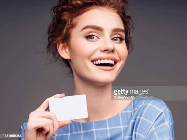 young woman holding a business card - femininity stock pictures, royalty-free photos & images