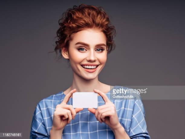young woman holding a business card - identity card stock pictures, royalty-free photos & images
