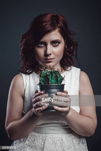 Young woman holding a cactus with a upset face