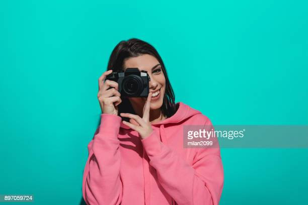 Young woman holding a camera while standing by a blue color background
