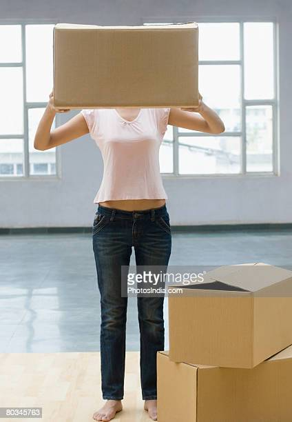Young woman holding a cardboard box in front of her face
