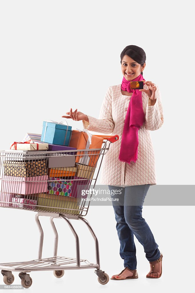 Young woman holding a cart full of gifts : Stock Photo