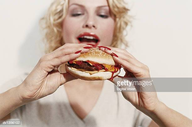 Young Woman Holding a Cheeseburger