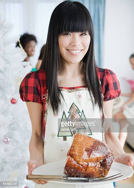 Young Woman holding a Christmas Ham at Party