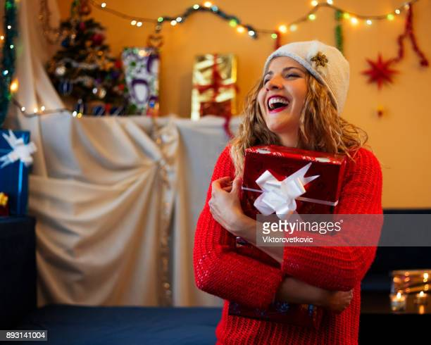 young woman holding a christmas present - santa face stock photos and pictures
