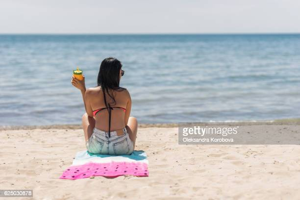 young woman holding a colorful drink cup on a beach. - istock images stock pictures, royalty-free photos & images
