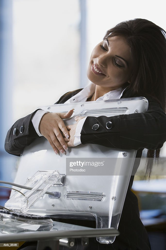 Young woman holding a computer monitor with her eyes closed : Stock Photo