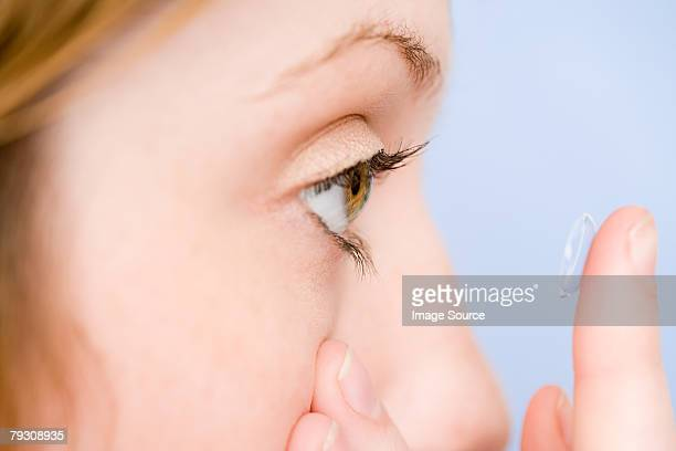 A young woman holding a contact lens
