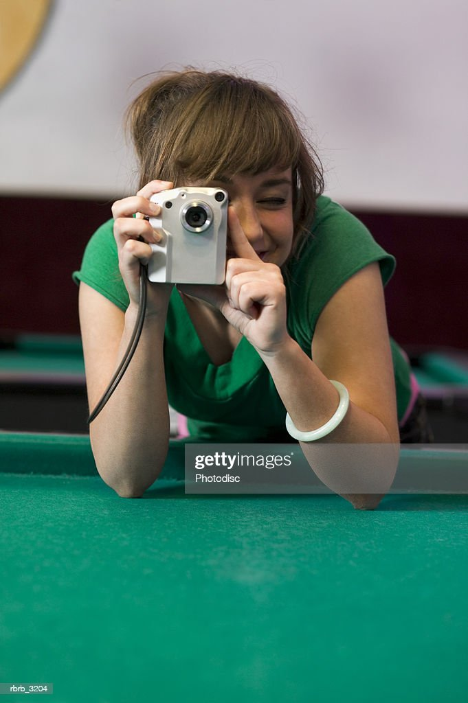 Young woman holding a digital camera over a pool table : Foto de stock