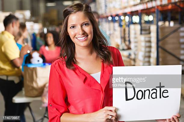 Young woman holding a Donate sign at toy food pantry