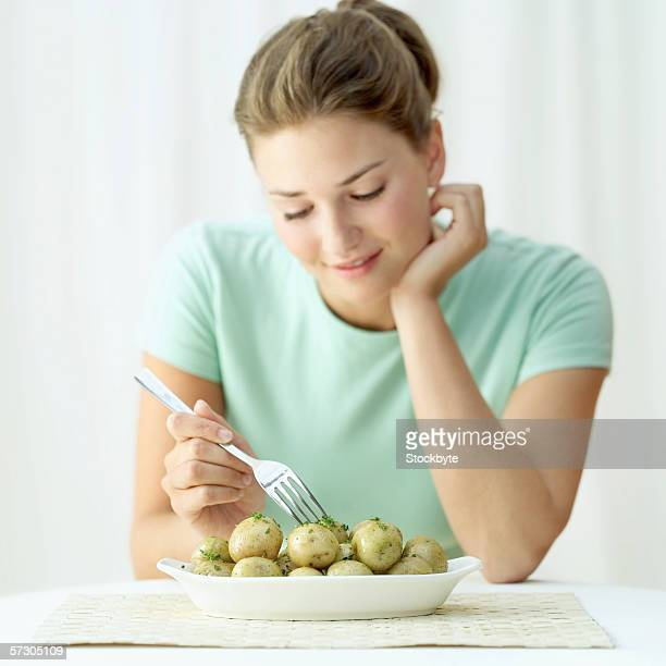 Young woman holding a fork in a dish of potatoes