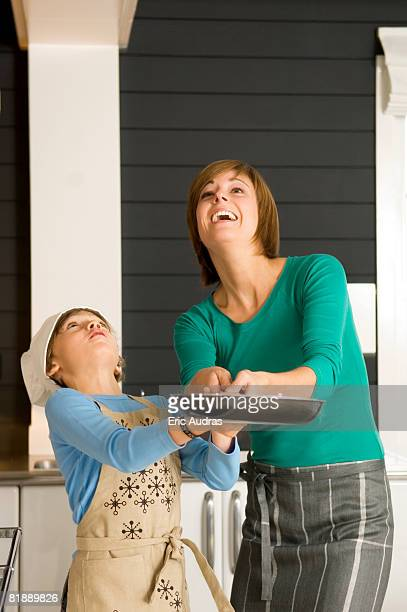 Young woman holding a frying pan with her son and smiling