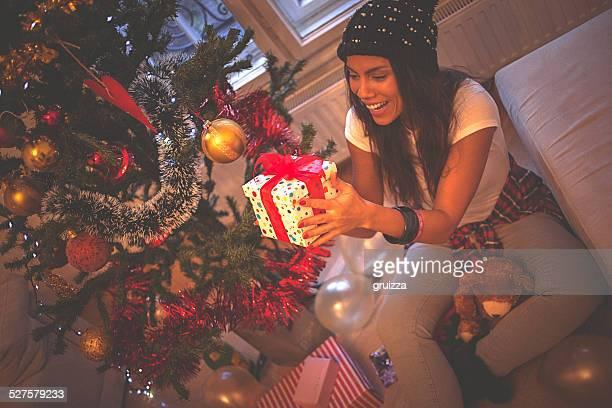 Jeune femme tenant la boîte-cadeau près de sapin de Noël