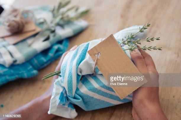 young woman holding a gift wrapped in reusable fabric - milieukwesties stockfoto's en -beelden
