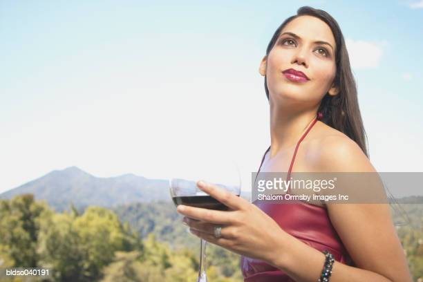 Young woman holding a glass of red wine looking up
